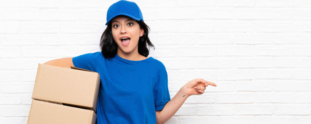 Young delivery woman over white brYoung delivery woman over white brick wall surprised and pointing finger to the sideick wall surprised and pointing finger to the side